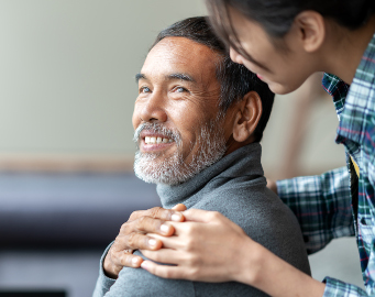 Smiling happy older Asian father with stylish short beard touching daughter's hand on shoulder looking and talking together with love and care.